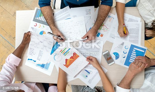 Unrecognizable group of business people in a meeting at the office looking at strategy documents