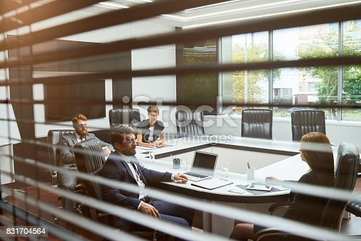 Group of business people listening to business partner at meeting in board room behind shutters