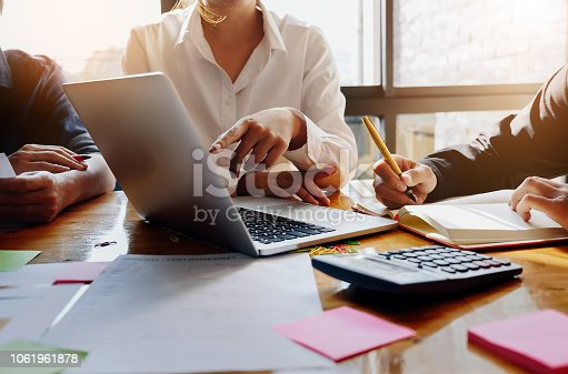 925942192istockphoto business meeting, business woman Explain analyze the company's sales plan to team leader and business owner by use computer laptop, calculator, stock market chart on wood desk in conference. 1061961878
