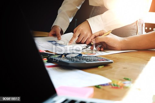 925942192istockphoto business meeting, business woman Explain analyze the company's sales plan  and business owner by use pen pointing stock market chart with calculator on wood desk in conferance. 909818512