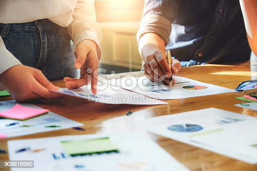 925942192istockphoto business meeting, business woman Explain analyze the company's sales plan  and business owner by use pen pointing stock market chart on wood desk in conferance. 909818560