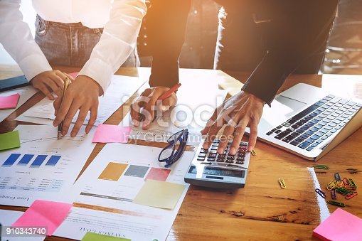881542122istockphoto business meeting, business woman Explain analyze the company's sales plan  and business owner by use calculator,  with laptop computer on wood desk in conference. 910343740