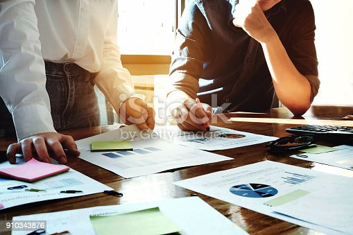 881542122istockphoto business meeting concept, calculate financial & budget & stock market data document with calculator in working on wood desk in office. 910343876