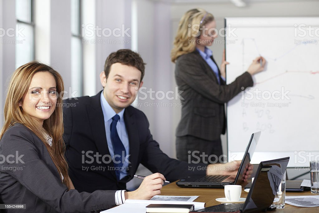 Business meeting, female presents graphs in background royalty-free stock photo
