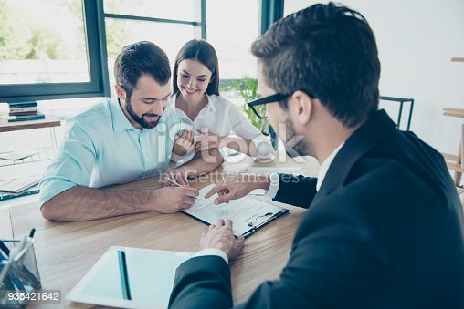 istock Business meeting. Happy couple is buying new house, young bearded attractive brunet lawyer in a formal wear is presenting contract to sign, they are in his office 935421642