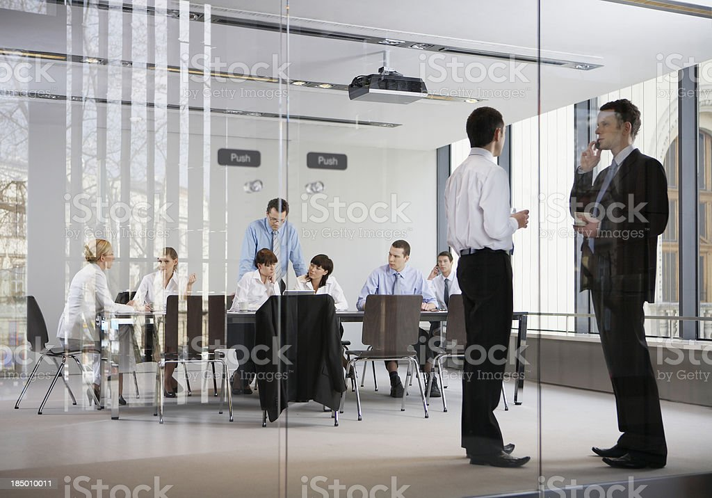 Business meeting in an office behind glass walls stock photo
