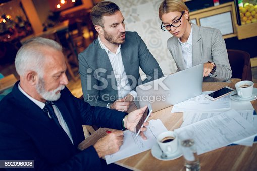 Group of three mixed age business people is discussing business in a meeting in cafe.