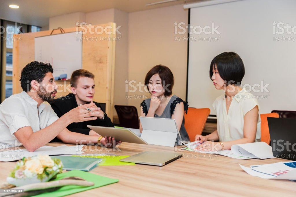 Group of business executives together in a meeting discussing the...