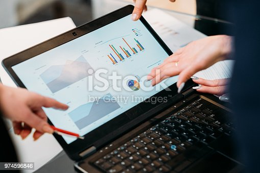 business meeting. problem solving, issue management. troubleshooting. communication, information exchange. executives discussing company results reading papers with graphical data on laptop