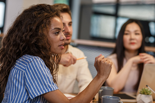 Side view of a group of multicultural entrepreneurs having a business meeting in a shared office space. Curly young woman lead the conference.