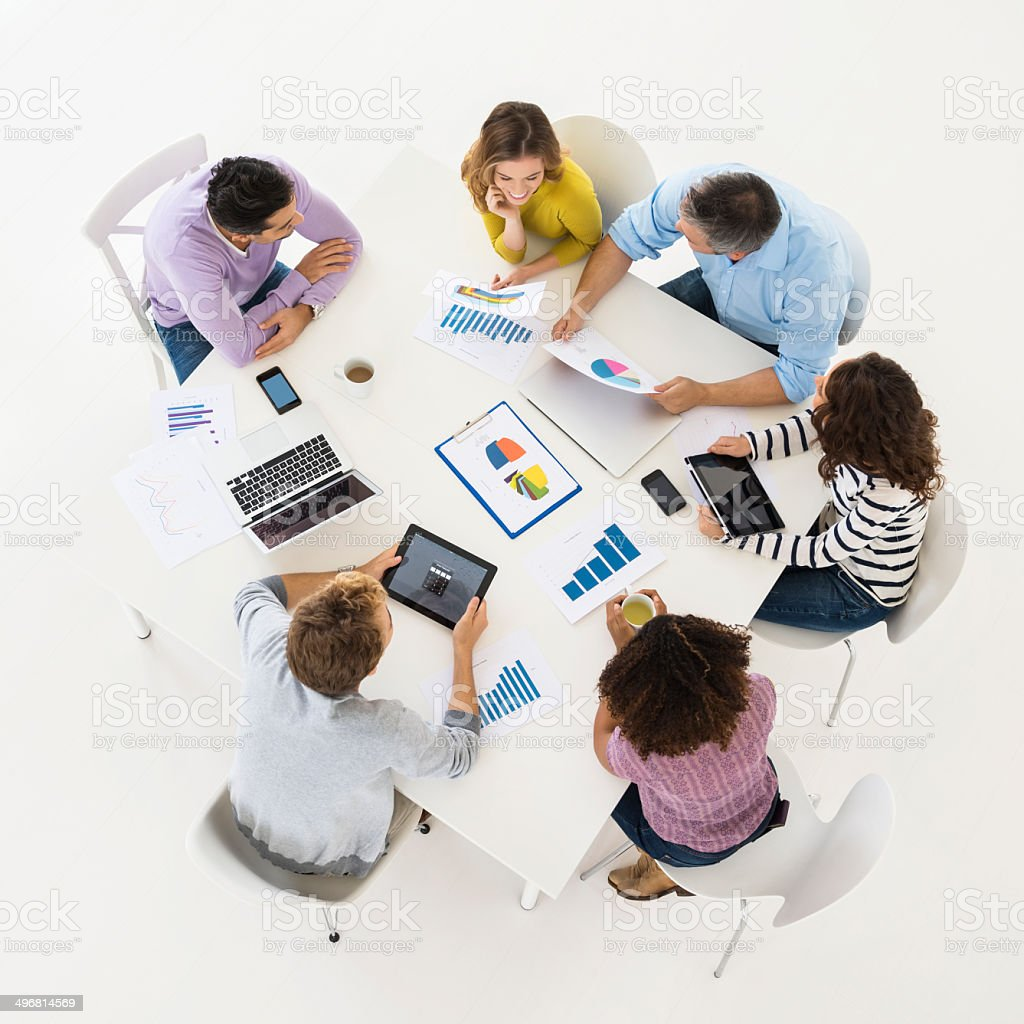 High angle overhead view of business people discussing in board room...
