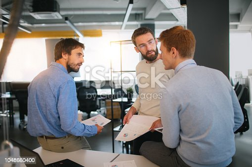 Group of young businessmen discussing on meeting in the office.