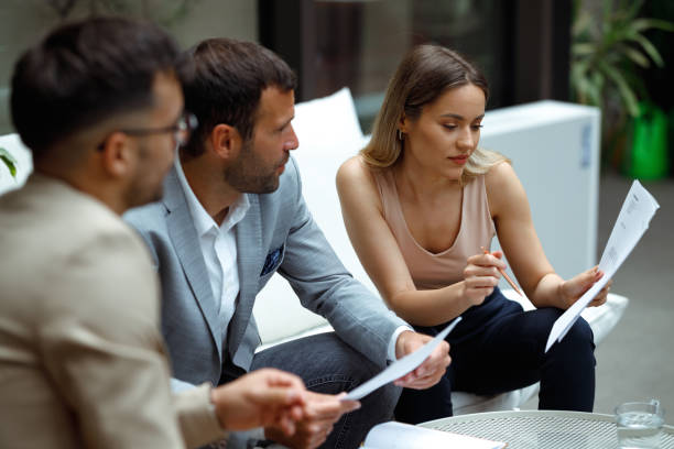 Business meeting Shot of three people at a meeting in the foyer of the company's building. The female boss is assigning the jobs to the employees. georgijevic coworking stock pictures, royalty-free photos & images