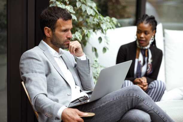Business meeting Two colleagues are trying to solve some business problem at a non-formal meeting at a foyer of a company's building. georgijevic coworking stock pictures, royalty-free photos & images