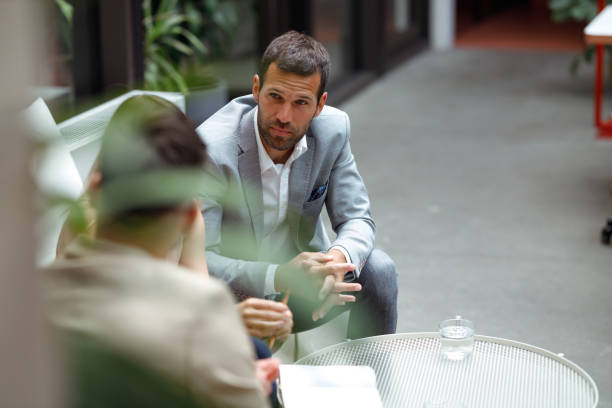 Business meeting Three colleagues are at a meeting in the foyer of the company's building. One of them is explaining new business strategies to the other two. georgijevic coworking stock pictures, royalty-free photos & images