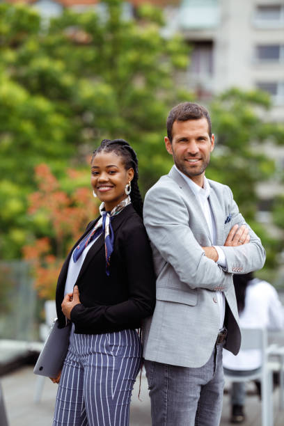 Business meeting Two business people are posing back to back on an outdoor space. georgijevic coworking stock pictures, royalty-free photos & images