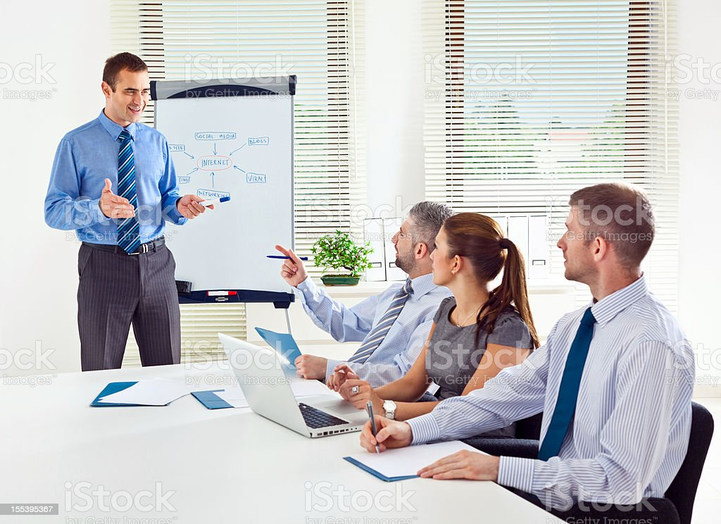 Business meeting Business team having a brainstorming in a boardroom, discussing new strategy of their company. Adult Stock Photo