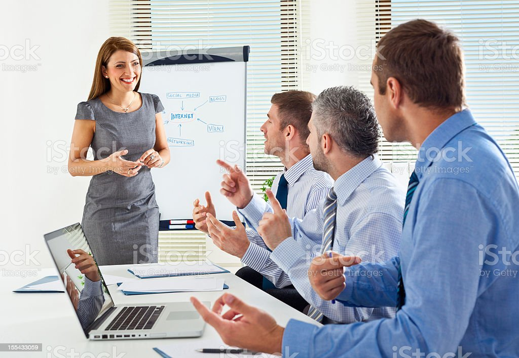 Business meeting Happy businesswoman having presentation in a board room, discussing with her business colleagues. Adult Stock Photo