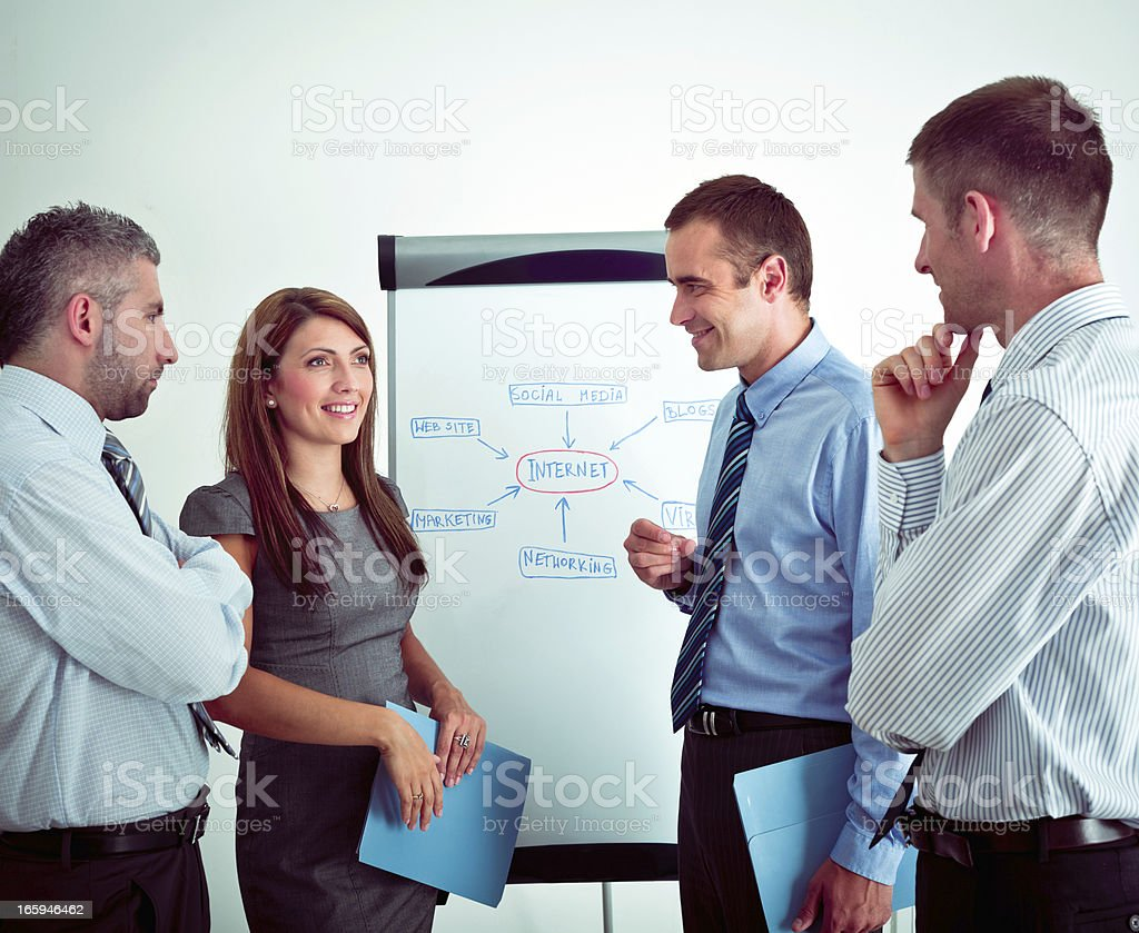 Business meeting Four happy business people discussing in a boardroom. 30-34 Years Stock Photo