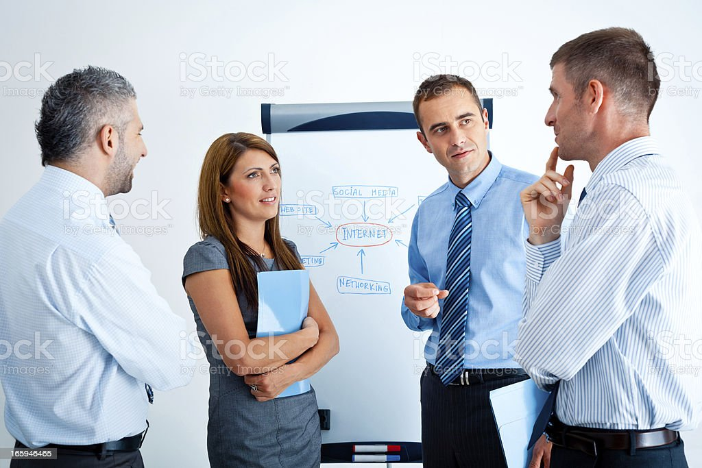 Business meeting Four business people discussing next to flipchart in an office. 30-34 Years Stock Photo