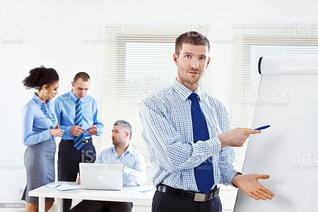 Business meeting Focus on businessman giving presentation on the flip chart and looking at camera with his colleagues working in the background. Adult Stock Photo