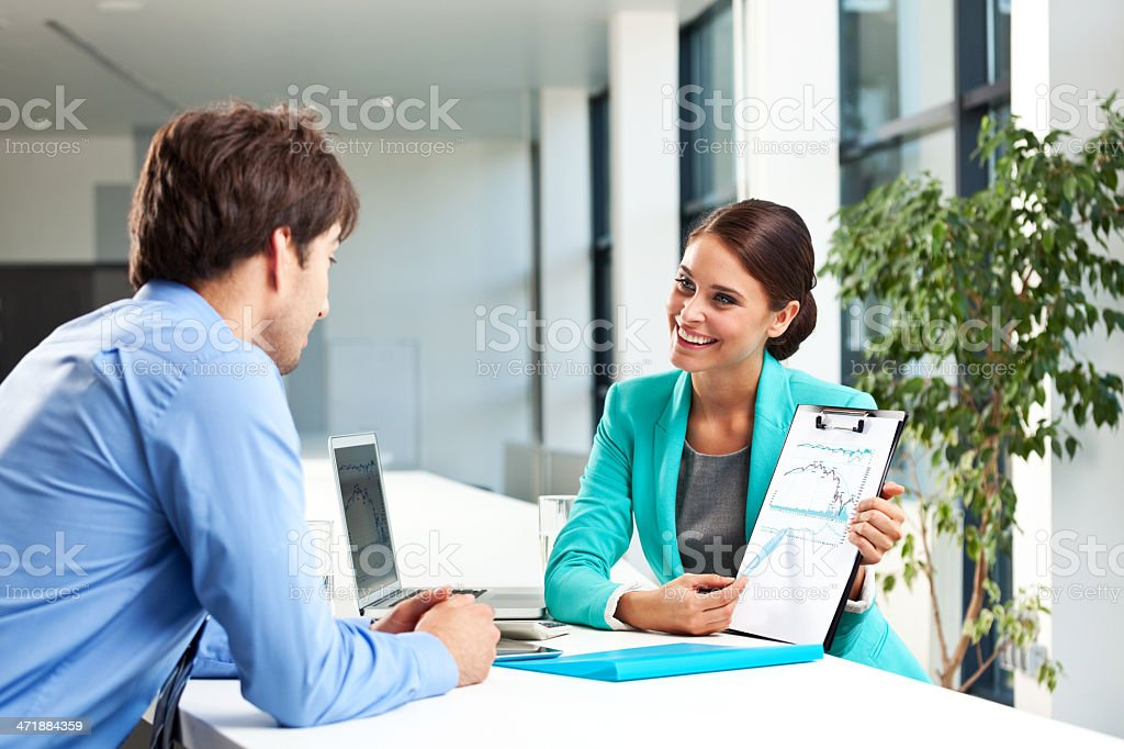 Business meeting Man having meeting with a financial advisor. Businesswoman showing him a graph. Adult Stock Photo