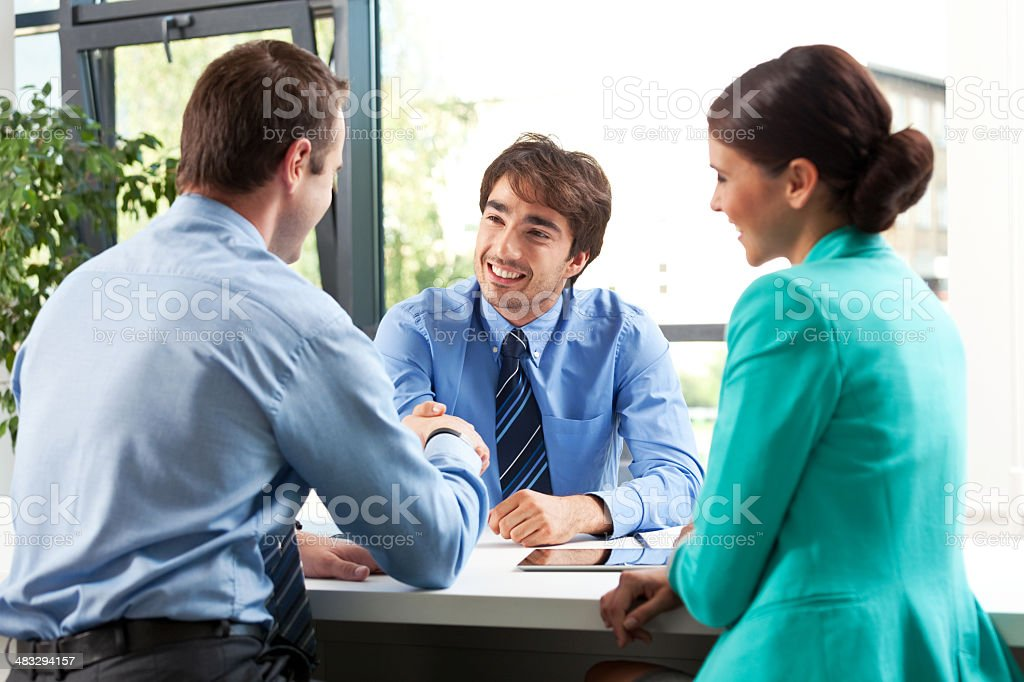 Business meeting Adult couple having meeting with business consultant. Men shaking hands. Adult Stock Photo