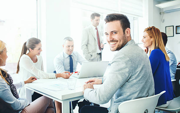 Business meeting. Closeup of smiling mid 30's businessman looking at camera while there's office meeting going on in background. There are sic of his coworkers sitting by the desk, one senior colleague is preparing for presentation speech. staff meeting stock pictures, royalty-free photos & images