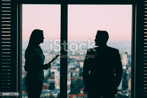 Two business people discussing a problem at the window of an office.