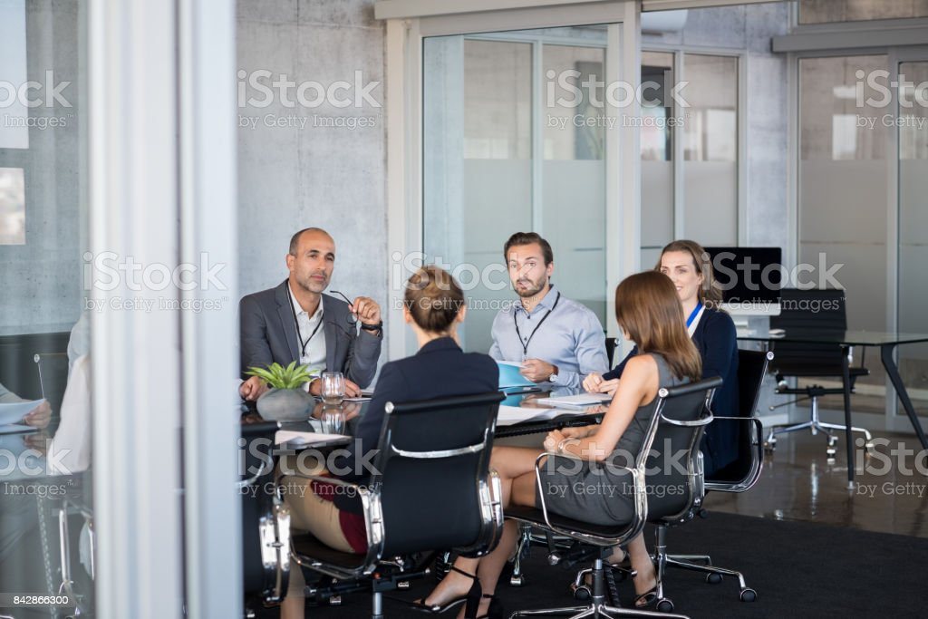 Business meeting Business people sitting in boardroom and working together at new strategy plan. Group of leader and businesspeople in a meeting at office. Senior executive with his team working in a conference room. Adult Stock Photo