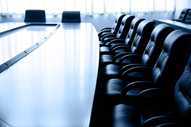 Business meeting room with large table and black chairs stock photo