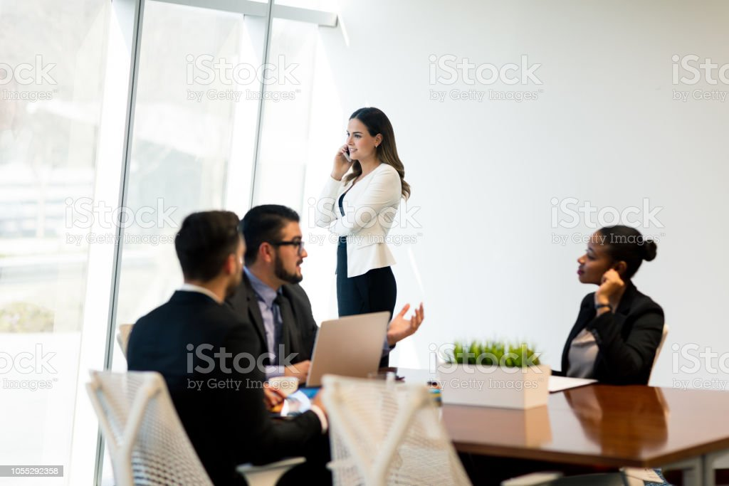 Business meeting with executive talking on phone in background stock photo