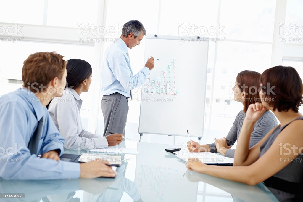 Business meeting with man writing on a whiteboard royalty-free stock photo