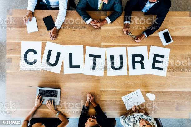 Top view of business people with word Culture on table. Business people having a meeting and discussing over work culture in office.