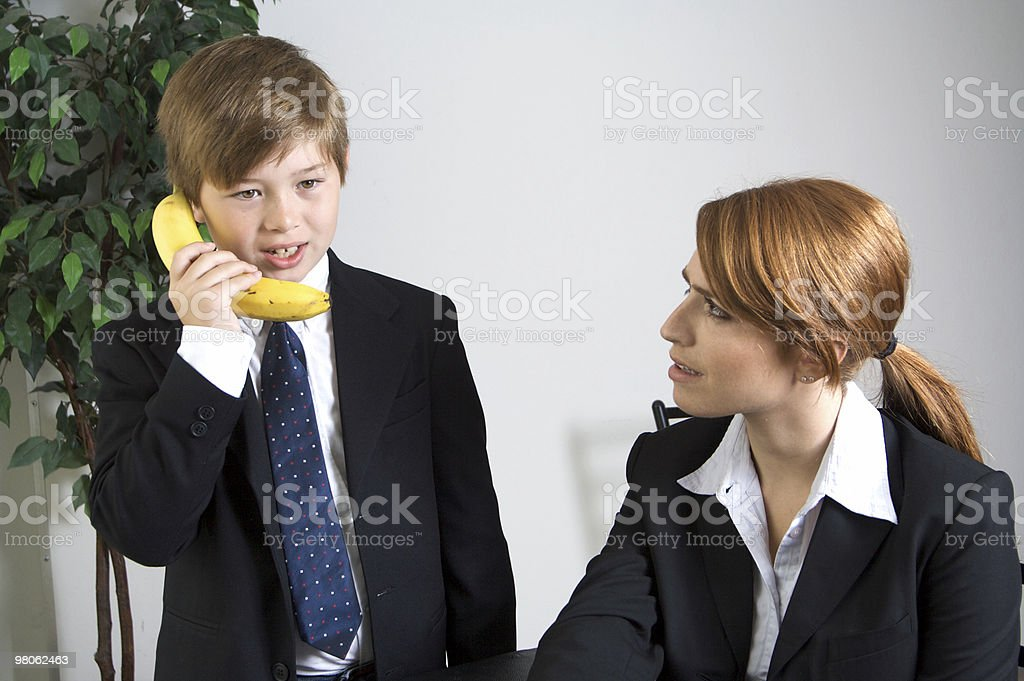 Business Meeting with Young Boy in Suit on Banana Phone royalty-free stock photo