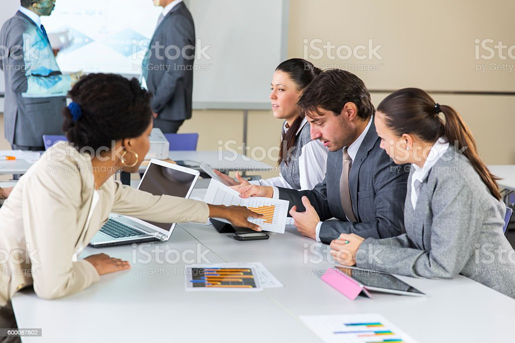 Business meeting.....black lecturer using digital projector,home made slide stock photo