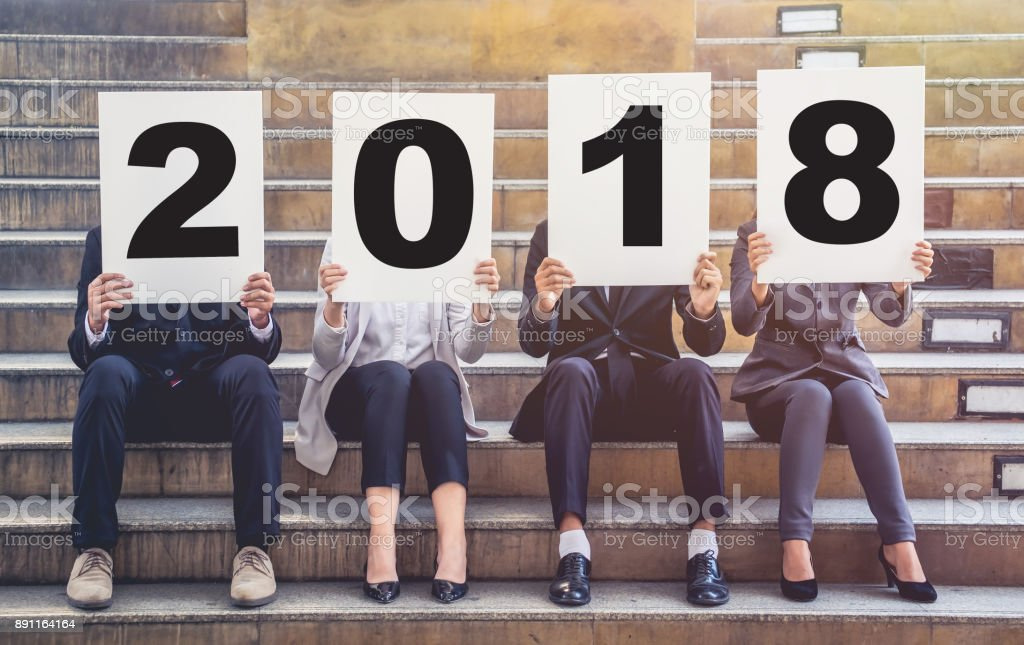 business men and women holding a sign saying 2018 and the upcoming new year