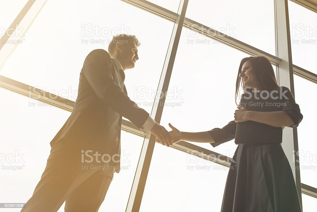 Business men and women shaking hands with a smile stock photo