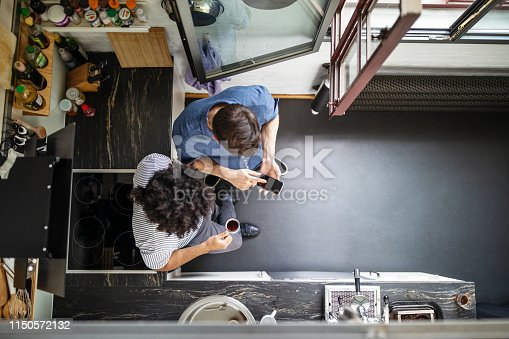 Top view of businessman showing smart phone to male colleague. Male professional with curly hair drinking coffee and looking at mobile phone of coworker.