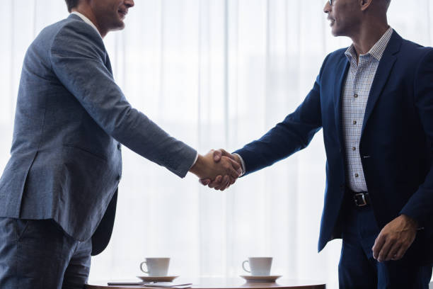 Business men shaking hands with each other after a deal Two business men shaking hands with each other after a deal. Businesspeople shaking hands making a necessary agreement during a meeting. dealing cards stock pictures, royalty-free photos & images
