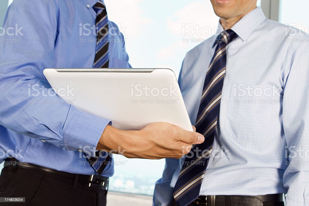 Business men sharing information on digital tablet royalty-free stock photo