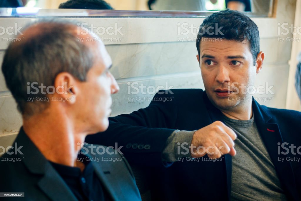 Business men talking sitting on a couch stock photo