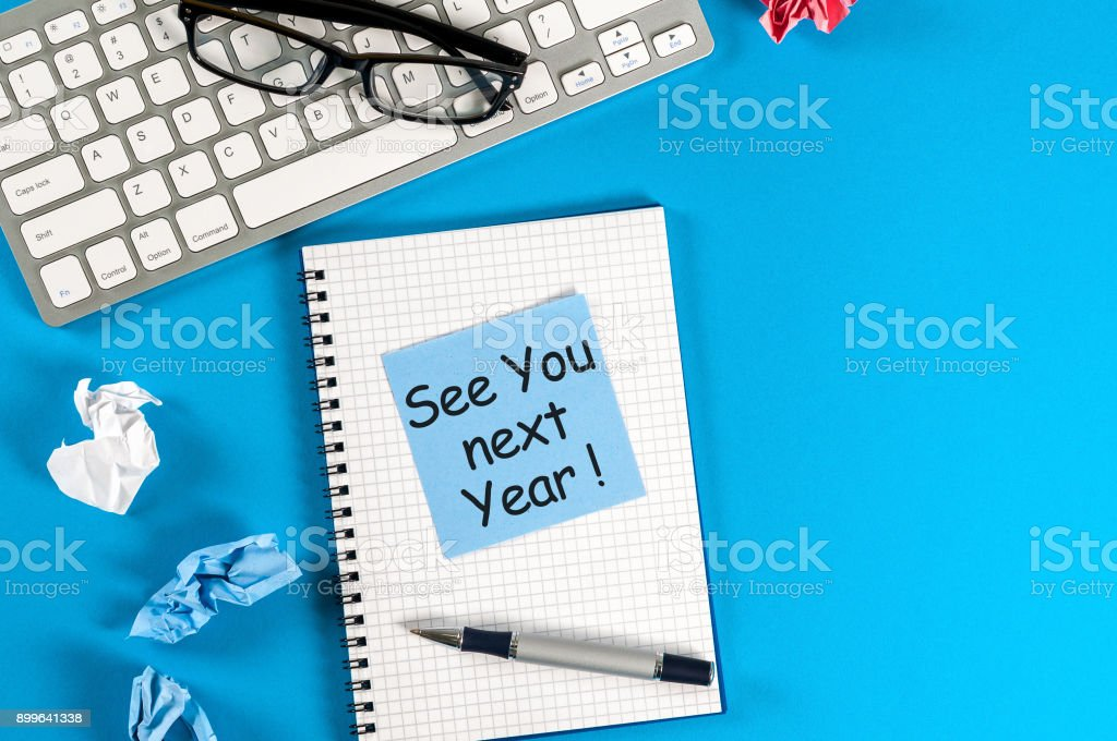 Business message See You Next Year written on notebook, with keyboard, office supplies and empty space at blue table in background stock photo