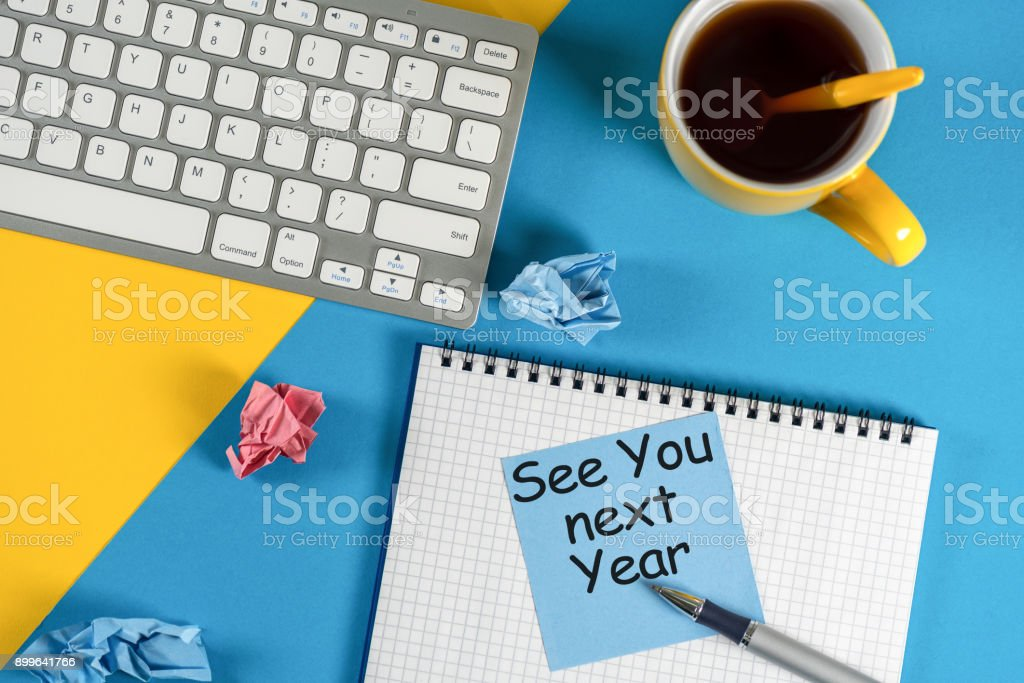 Business message See You Next Year written on notebook, with keyboard, office supplies at blue table in background stock photo