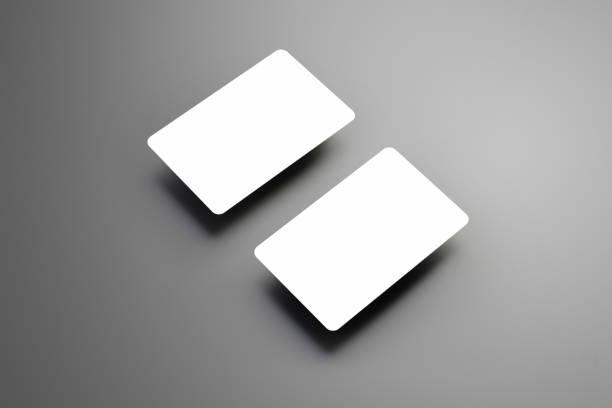 business modell zwei leere bank (geschenk) karten auf ein studio grauen hintergrund isoliert. - gutschein ausdrucken stock-fotos und bilder