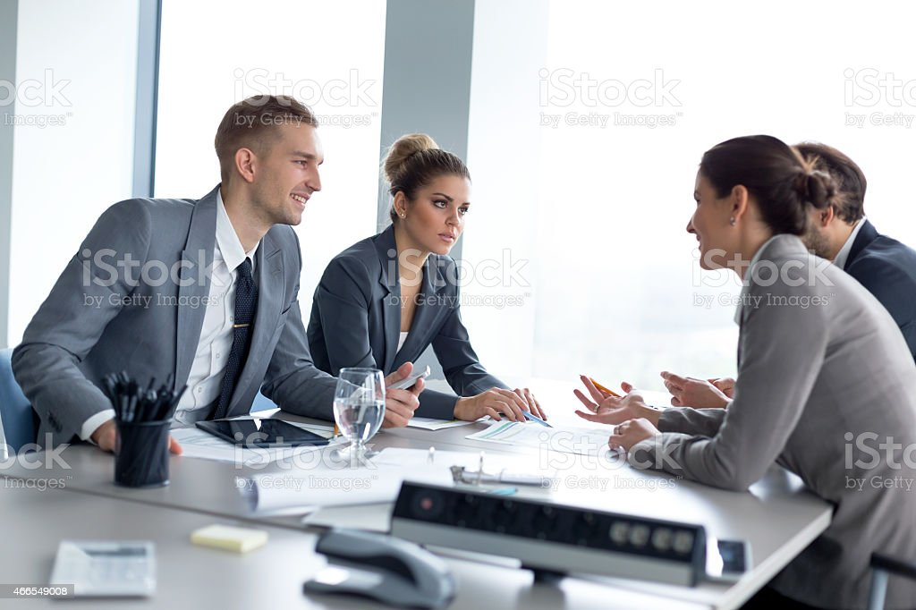 Successful business people on a negotiation meeting pointing at the...
