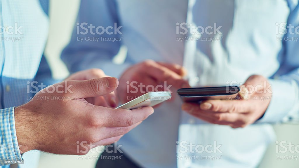 Two men holding smart phones and exchanging mobile contacts