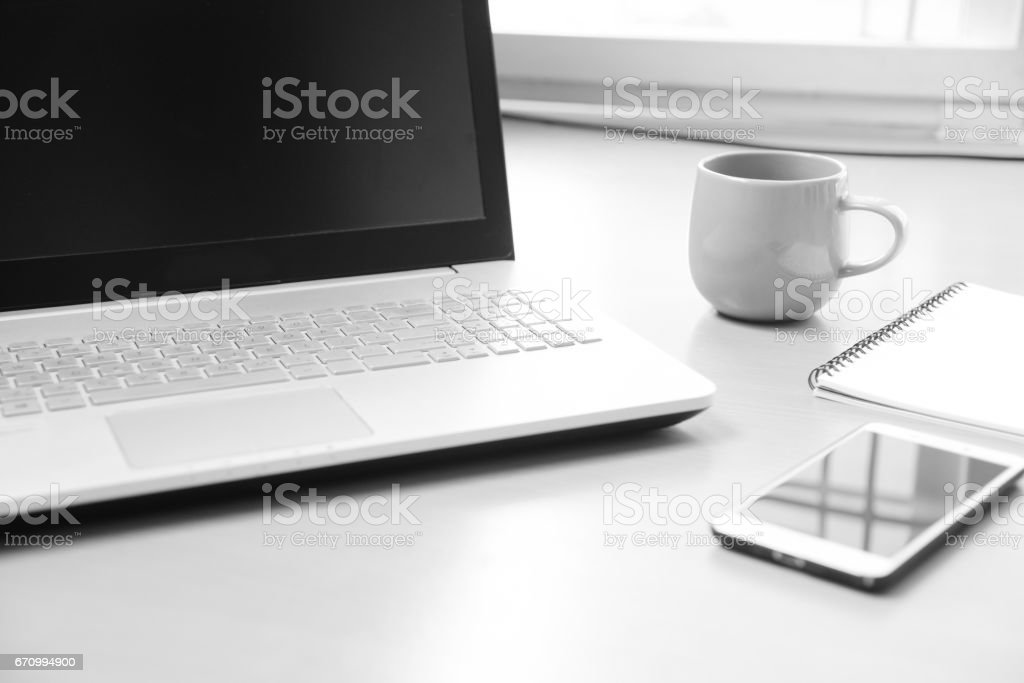 Business Notebook computer with smart phone , notebook paper for note message and a cup of coffee on wood desk background ( soft focus black and white photo ) stock photo