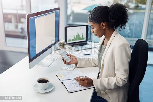 Shot of a young businesswoman using a mobile phone at her desk in a modern office