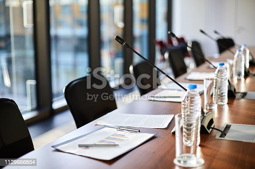 Business documents, plastic bottles of water, glasses and microphones along table and chairs near by in conference hall